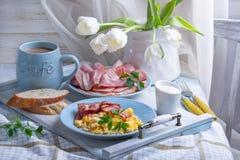 Prima colazione con le uova rimescolate, il bacon e un mazzo immagine stock