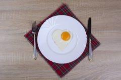 Prima colazione con le uova rimescolate sotto forma di cuore Fotografie Stock