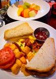 Prima colazione con pane tostato, le uova rimescolate, il pomodoro ed i frutti Fotografia Stock Libera da Diritti