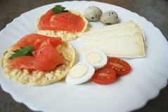 Prima colazione: cracker del riso con il salmone, uova di quaglia, formaggio, pomodori Fotografie Stock Libere da Diritti