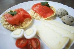 Prima colazione: cracker del riso con il salmone, uova di quaglia, formaggio, pomodori Fotografia Stock Libera da Diritti