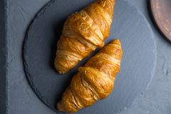 Prima colazione, croissant tradizionali al forno freschi, su un piatto dell'ardesia sopra il fondo nero di struttura Vista superi immagini stock