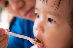 Prima colazione d'alimentazione della madre alla ragazza Fotografia Stock