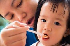 Prima colazione d'alimentazione della madre alla ragazza Immagine Stock Libera da Diritti
