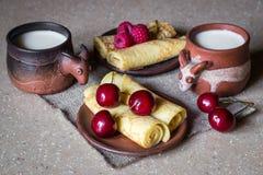Prima colazione dei pancake rotolati con le bacche ed il latte, natura morta Immagini Stock