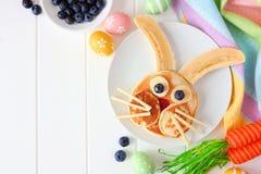 Prima colazione del pancake del coniglietto di pasqua, confine d'angolo contro un fondo di legno bianco fotografia stock