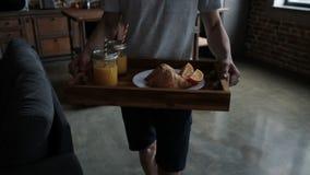 Prima colazione del servizio dell'uomo sul vassoio di legno a letto stock footage