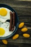 Prima colazione deliziosa casalinga con sul piatto l'uovo fritto, salsiccia, pomodori nella vista superiore fotografia stock