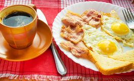 Prima colazione deliziosa - una tazza di caff?, un piatto delle uova fritte, bacon e pane tostato, accanto alla coltelleria sul t fotografia stock libera da diritti