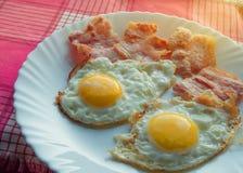 Prima colazione deliziosa - uova fritte, bacon delizioso su un piatto bianco fotografia stock libera da diritti
