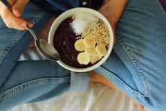 Prima colazione della ciotola nel letto Ragazza della prima colazione una ciotola immagine stock