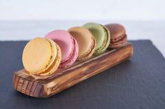Prima colazione della stecca di legno dei macarons fotografia stock