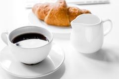 Prima colazione di affari in ufficio con latte, caffè ed il croissant sopra Immagini Stock