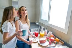 Prima colazione di anni dell'adolescenza delle ragazze dei migliori amici in cucina Immagine Stock