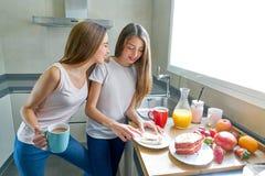Prima colazione di anni dell'adolescenza delle ragazze dei migliori amici in cucina Immagini Stock