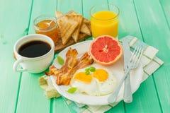 Prima colazione di estate - uova, bacon, pane tostato, inceppamento, caffè, succo fotografie stock