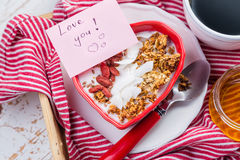 Prima colazione di giorno del ` s del biglietto di S. Valentino - granola con yogurt, le bacche di goji e la noce di cocco Fotografie Stock