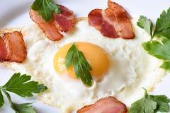 Prima colazione di mattina con le uova fritte con bacon e prezzemolo leggermente fritti su un piatto bianco fotografia stock libera da diritti