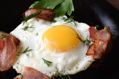 Prima colazione di mattina con le uova fritte con bacon e prezzemolo leggermente fritti su un piatto posteriore immagini stock