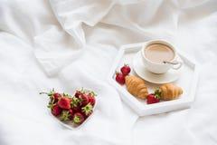 Prima colazione di primo mattino a letto, caffè e croissant con strawb fotografia stock