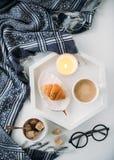 Prima colazione domestica accogliente, coperta calda, caffè e croissant su bianco immagini stock