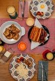 Prima colazione domestica di stile con bacon croccante, le uova, il pane tostato francese, la salsiccia ed il succo d'arancia fotografia stock