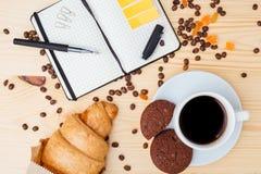 Prima colazione e blocco note dolci in un disordine sulla tavola Immagini Stock Libere da Diritti