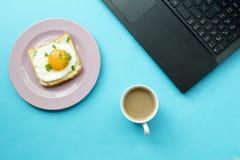 Prima colazione e computer portatile su fondo blu fotografie stock libere da diritti