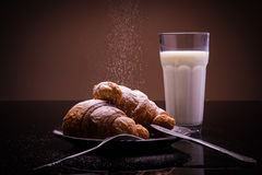 Prima colazione francese; croissant su un piatto con zucchero e bicchiere di latte in polvere Immagine Stock