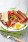 Prima colazione inglese con i fagioli dei pomodori del bacon delle salsiccie dell'uovo fritto Fotografia Stock