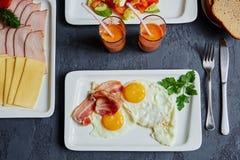Prima colazione inglese con le uova ed il bacon rimescolati, succo di carota, b fotografie stock libere da diritti