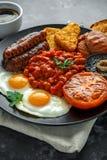 Prima colazione inglese piena con bacon, la salsiccia, l'uovo fritto, i fagioli in salsa, le patate grattugiate/in padella ed i f fotografia stock libera da diritti