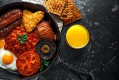 Prima colazione inglese piena con bacon, la salsiccia, l'uovo fritto, i fagioli in salsa, le patate grattugiate/in padella ed i f fotografia stock