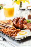 Prima colazione inglese piena con bacon, salsiccia, uovo, fagioli in salsa e Immagini Stock