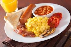 Prima colazione inglese piena con le uova rimescolate, bacon, salsiccia, fagiolo immagine stock