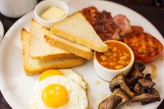 Prima colazione inglese piena tradizionale con le uova sul piatto fritte, bacon, salsiccie, fagioli in salsa al pomodoro, pani to immagini stock