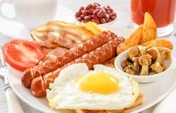 Prima colazione inglese piena - uovo fritto, salsiccie, bacon, fagioli Un vetro di succo fresco Una tazza di tè al latte immagini stock libere da diritti