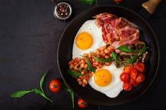 Prima colazione inglese - uovo fritto, fagioli, pomodori, funghi, bacon e pane tostato immagine stock