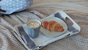 Prima colazione a letto con caffè e un croissant per una giovane donna attraente archivi video