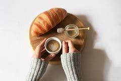 Prima colazione a letto posta pianamente Mano della donna che tiene tazza di caffè, taglio di legno con il croissant fresco e mie immagine stock libera da diritti