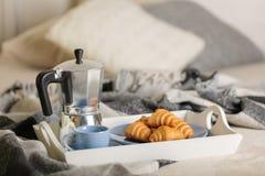 Prima colazione a letto Su un vassoio bianco ci sono una macchinetta del caffè, una tazza ed i croissant blu del caffè immagini stock libere da diritti