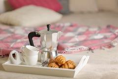 Prima colazione a letto Su un vassoio di vimini bianco c'è una macchinetta del caffè fotografie stock libere da diritti