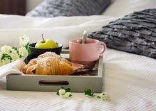 Prima colazione a letto Una tazza di caffè, croissant su un vassoio, un appl immagine stock libera da diritti