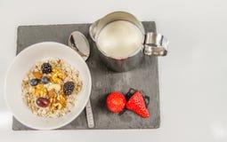 Prima colazione nutriente della farina d'avena con frutta con una brocca di latte sopra fotografia stock libera da diritti