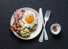 Prima colazione nutriente sana - pane tostato dell'avocado, bacon ed uovo fritto su fondo scuro immagine stock