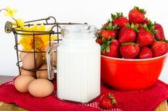 Prima colazione nutrizionale delle uova marroni, delle fragole e del latte Fotografia Stock