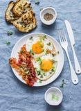 Prima colazione o spuntino tradizionale - le uova fritte, bacon, hanno grigliato il pane su fondo blu, vista superiore immagini stock