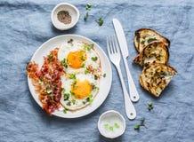 Prima colazione o spuntino tradizionale - le uova fritte, bacon, hanno grigliato il pane su fondo blu, vista superiore immagine stock