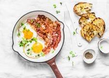 Prima colazione o spuntino tradizionale - le uova fritte, bacon, hanno grigliato il pane su fondo leggero, vista superiore fotografia stock libera da diritti