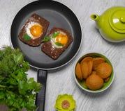Prima colazione - pane tostato con il pomodoro del formaggio fuso, le uova fritte, le uova fritte, la teiera e la tazza di tè su  Immagini Stock